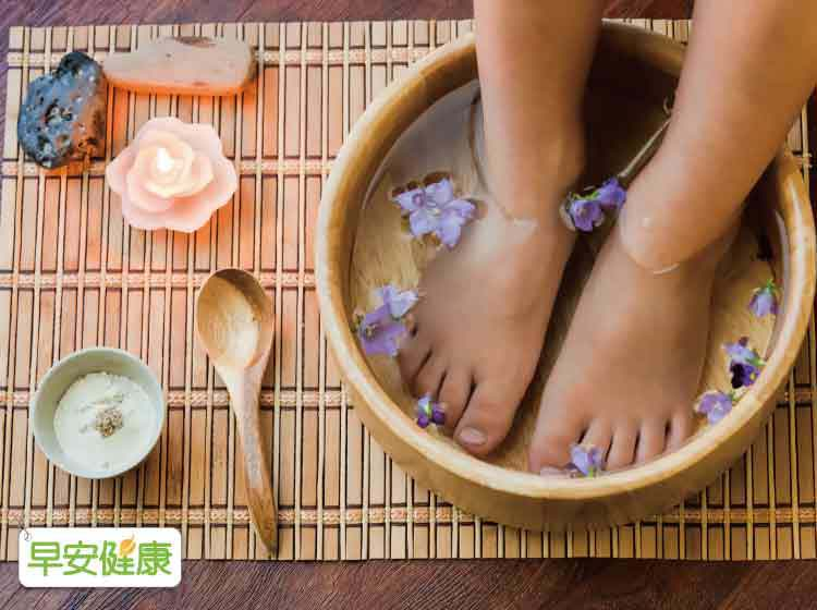 A person soaks their feet in a wooden bowl of water with flower pedals and a lit candle and herb powder to the side.